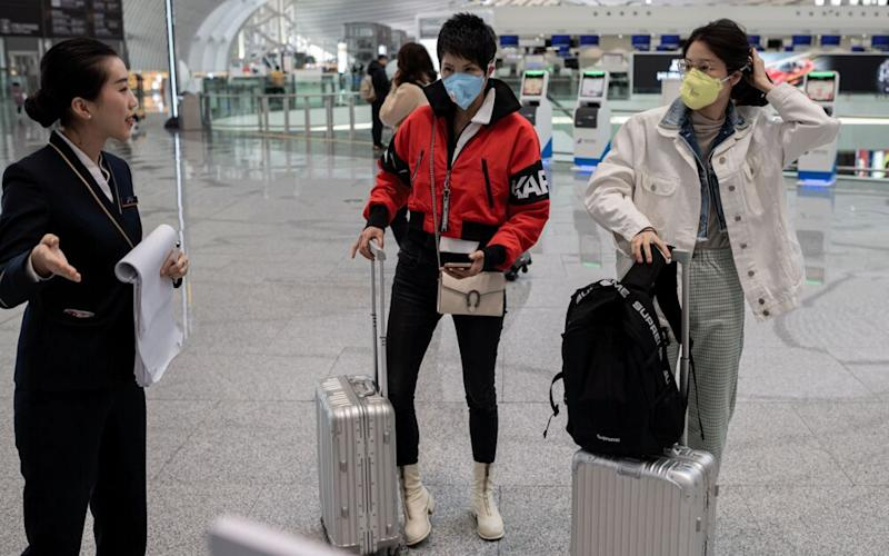 Travelers wearing protective masks at the Daxing international airport in Beijing. | Getty Images