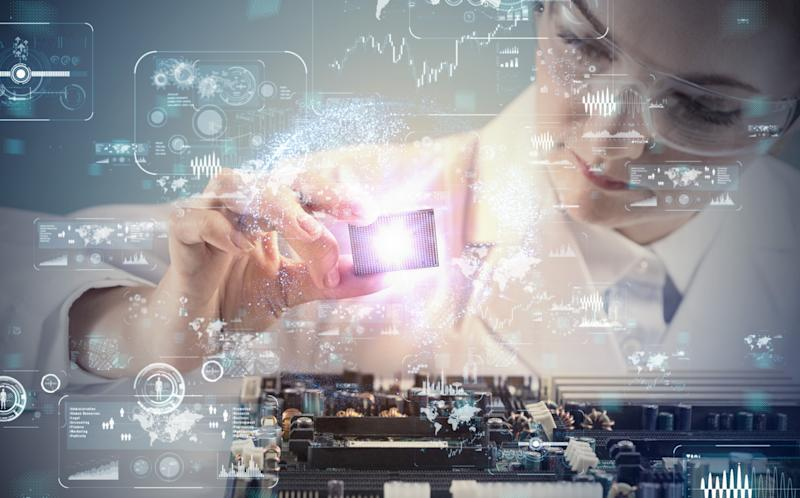 A young woman lifts a computer chip from a machine, overlaid by various symbols.