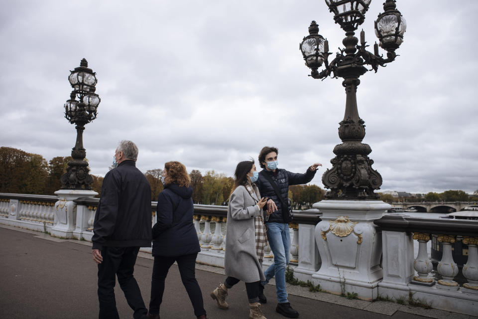 People wearing masks, walk on Alexandre III bridge in Paris, Sunday Oct.25, 2020. A curfew intended to curb the spiraling spread of the coronavirus, has been imposed in many regions of France including Paris and its suburbs. (AP Photo/Lewis Joly)