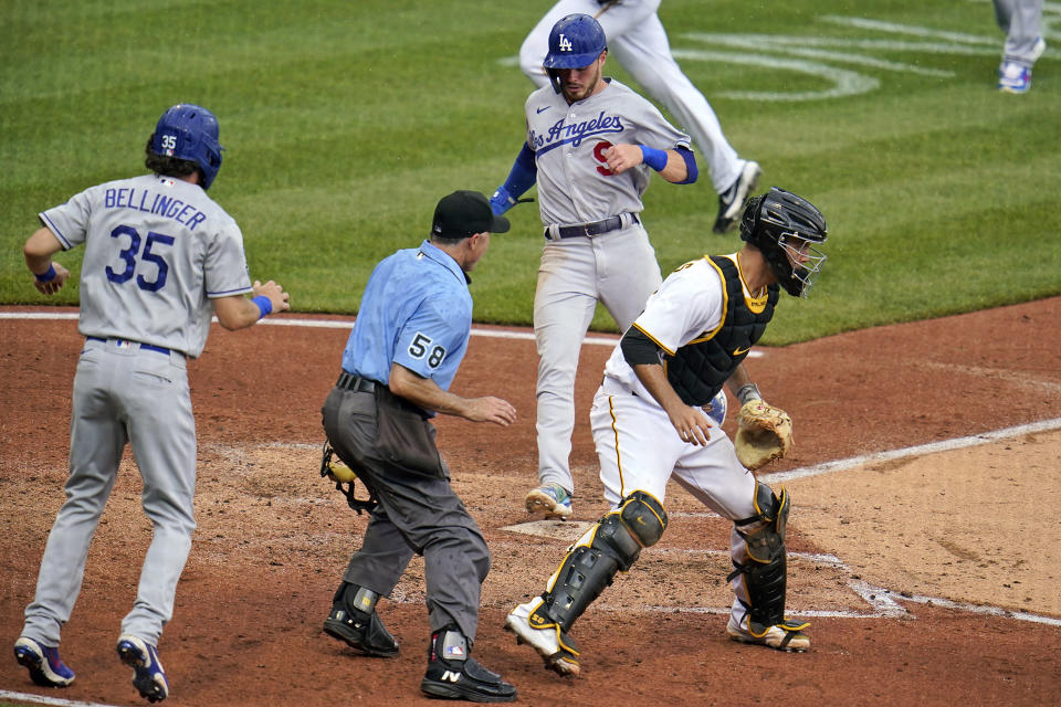 Los Angeles Dodgers' Cody Bellinger, left, watches, after scoring, as Gavin Lux, center, scores as Pittsburgh Pirates catcher Jacob Stallings, right, waits for the late relay throw during the third inning of a baseball game in Pittsburgh, Thursday, June 10, 2021. Umpire is Dan Iassogna (58). (AP Photo/Gene J. Puskar)