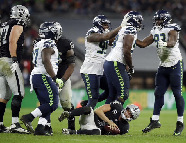FILE - In this Oct. 14, 2018, file photo, Seattle Seahawks players react after sacking Oakland Raiders quarterback Derek Carr, bottom center, during the second half of an NFL football game at Wembley stadium in London. Carr has already been sacked 24 times halfway through the season for the Raiders (1-7), a mark he has topped only once in an entire season in his first four seasons.(AP Photo/Matt Dunham, File)