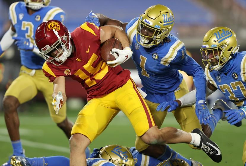 PASADENA, CALIFORNIA - DECEMBER 12: Drake London #15 of the USC Trojans runs past Jay Shaw #1 and Quentin Lake #37 of the UCLA Bruins for a touchdown during the first half of a game at the Rose Bowl on December 12, 2020 in Pasadena, California. (Photo by Sean M. Haffey/Getty Images)