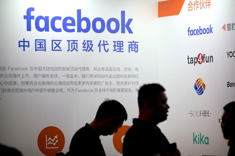 "Visitors walk past the Facebook logo at an exhibitor's display at the Global Mobile Internet Conference (GMIC) in Beijing, Thursday, April 26, 2018. The GMIC features current and future trends in the mobile Internet industry by some major foreign and Chinese internet companies. The text reads ""first-rate commercial agent for China"". (AP Photo/Mark Schiefelbein)"