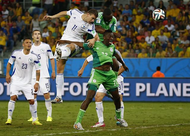 Bosnia's Edin Dzeko heads the ball next to Nigeria's Kenneth Omeruo (22) and Shola Ameobi as he misses a chance to score a goal during their 2014 World Cup Group F soccer match at the Pantanal arena in Cuiaba June 21, 2014. REUTERS/Michael Dalder (BRAZIL - Tags: SPORT SOCCER WORLD CUP TPX IMAGES OF THE DAY)