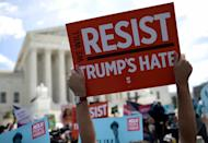 <p>Protesters hold up signs that read 'We Will Resist Trump's Hate' against U.S. President Trump's travel ban gather outside the U.S. Supreme Court as the court issued an immigration ruling June 26, 2018 in Washington, D.C. (Photo: Win McNamee/Getty Images) </p>