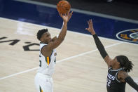 Utah Jazz guard Donovan Mitchell, left, shoots as Sacramento Kings center Richaun Holmes (22) defends in the first half during an NBA basketball game Saturday, April 10, 2021, in Salt Lake City. (AP Photo/Rick Bowmer)