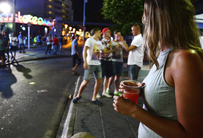 FILE - In this June 10, 2015 file photo, tourists stand on the street in Magaluf, Calvia on the Spanish Balearic island of Mallorca, Spain. Authorities in Spain´s tourist-magnet Balearic Islands are clamping down on binge-drinking tourism in three hot-spots. The regional government has passed a law prohibiting the organization and promotion of pub crawls and publicity promoting the consumption of alcohol by means of 'open bars' and 'happy hours'. (AP Photo/Joan Llado, File)