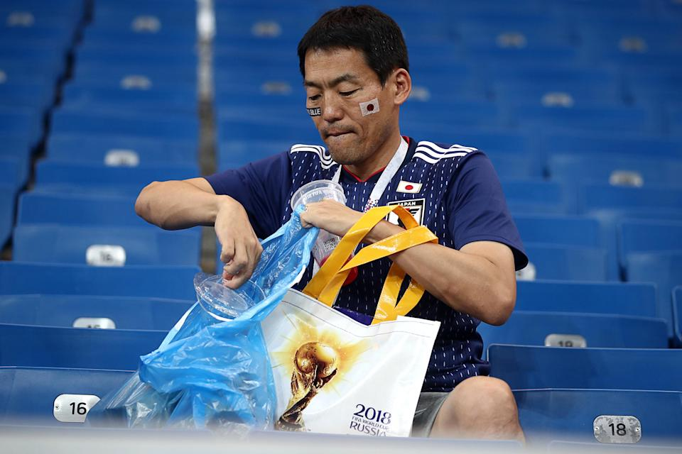 Japan's supporter picking up litter after their 2018 FIFA World Cup Round of 16 football match against Belgium at Rostov Arena Stadium. (Getty)
