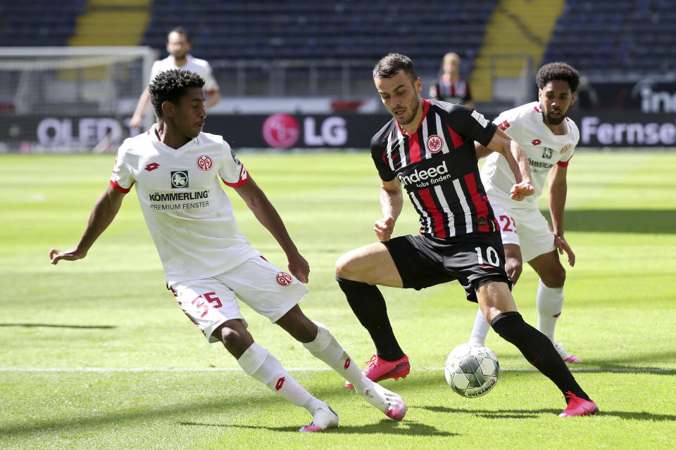 Mainz's Leandro Barreiro Martins, left, challenges Eintracht's Filip Kostic during the German Bundesliga soccer match between Eintracht and Mainz, in Frankfurt, Germany, Saturday, June 6, 2020. Because of the coronavirus outbreak all soccer matches of the German Bundesliga take place without spectators. (Alexander Hassenstein/Pool Photo via AP)