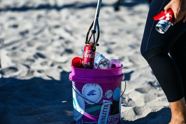 "Sophie Ringel, founder of the nonprofit organization ""Clean Miami Beach,"" collects trash left on the beach"