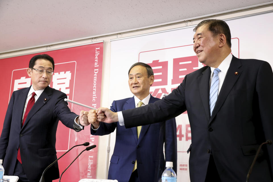 Three candidates for the ruling Liberal Democratic Party leadership, Japanese Chief Cabinet Secretary Yoshihide Suga, center, former Foreign Minister Fumio Kishida, left, and former Defense Minister Shigeru Ishiba, right, join their fists before starting a press conference at the party headquarters in Tokyo, Japan, Tuesday, Sept. 8, 2020. Official campaigning to choose outgoing Prime Minister Shinzo Abe's successor to lead his ruling party, who will almost certainly be Japan's next leader, kicked off Tuesday, with his long time right-hand man and top government spokesman now seen as a top candidate. (Yoshikazu Tsuno/Pool Photo via AP)