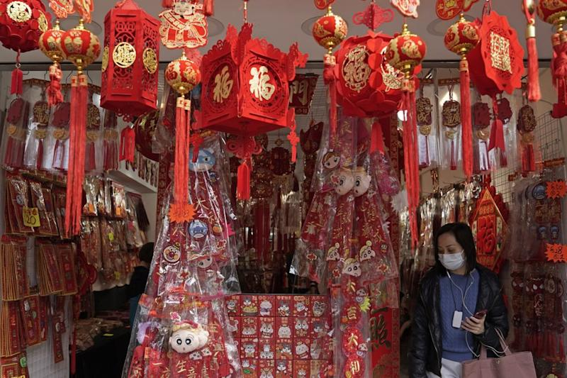 A woman wearing a face mask among Chinese New Year decorations in Hong Kong. The deadly outbreak comes as travel begins for the holiday.