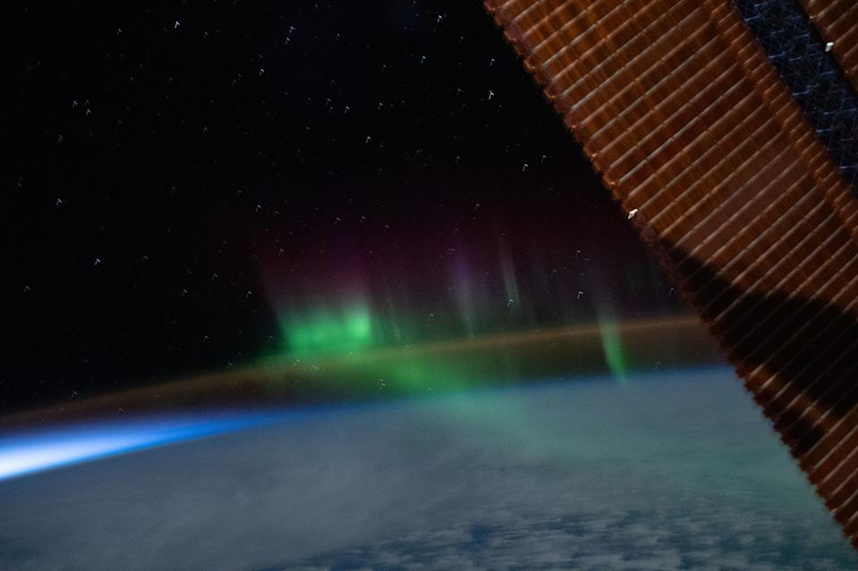 Green and purple auroras shimmy above the orange airglow of Earth's upper atmosphere in this colorful view from the International Space Station. NASA astronaut Chris Cassidy captured this image while the space station was orbiting above the Indian Ocean, between the continents of Australia and Antarctica, on June 7, 2020.