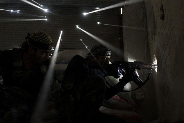 Two Syrian rebels take sniper positions at the heavily contested neighborhood of Karmal Jabl in central Aleppo on October 18, 2012. Violence persisted on October 19 with rebels and loyalists of President Bashar al-Assad locked in battle for the northwestern town of Maaret al-Numan on the Damascus-Aleppo highway linking Syria's two biggest cities. AFP PHOTO/JAVIER MANZANO
