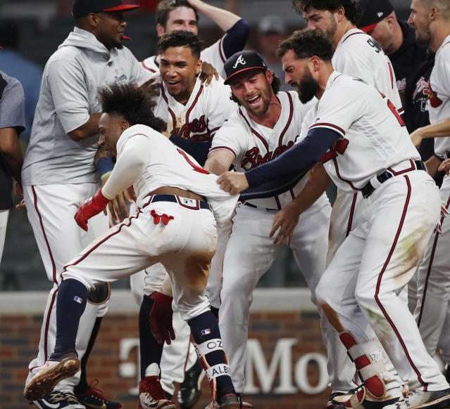 Atlanta Braves second baseman Ozzie Albies (1) is mobbed by his teammates after hitting a walk-off home run in the 11th inning of a baseball game against the Cincinnati Reds, Tuesday, June 26, 2018, in Atlanta. (AP photo/John Bazemore)