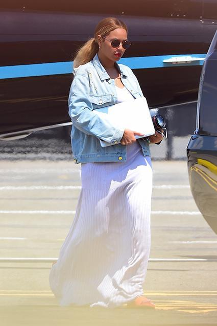 """Here we go again. Beyonce is, yet again, sparking pregnancy rumors as she touched down in New York City on Monday via helicopter, along with her husband, Jay Z, and 3-year-old daughter, Blue Ivy. Arriving at West 30th Street Heliport, the 33-year-old superstar was snapped covering her stomach with her laptop, while wearing a loose maxi dress and a baggy jean jacket. <strong>WATCH: Beyonce and Blue Ivy Wear Matching Shoes, Go for a Swim in Adorable New Photos</strong> 247PapsTV Naturally, some fans are now getting excited at the possibility that Queen Bey is expecting baby number two. OK! magazine touched off the latest pregnancy rumors last Thursday, citing a source that says Beyonce and Jay are expecting their second child after undergoing rounds of IVF treatment. It's also been a month since Beyonce posted her last full-body pic on Instagram, leading some to suspect she's hiding a possible baby bump. The last glimpse of her bikini body was also posted on July 1. And the timing couldn't be more perfect since we're less than a month away from the 2015 MTV Video Music Awards, taking place on August 30 in Los Angeles. Who could ever forget Beyonce's epic pregnancy announcement at the 2011 VMAs during her performance of """"Love on Top?!"""" <strong>WATCH: The 6 Best Pregnancy Announcements Ever</strong> Though, of course, this isn't the first Beyonce pregnancy rumor to persist. In January, her Destiny's Child band member, Michelle Williams, shut down rumors when fans picked up on an Instagram pic of the """"Flawless"""" singer buried in sand, with what appeared to be an oversize belly. Watch below:"""