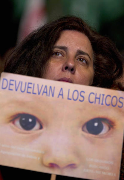 "A woman holds a sign that reads in Spanish ""Give the children back"" outside a court where Argentina's historic stolen babies trial is being held in Buenos Aires, Argentina, Thursday, July 5, 2012. Former dictators Jorge Videla and Reynaldo Bignone and a handful of other retired military and police officials are accused of systematically stealing babies from leftists who were kidnapped and killed when a military junta ran the country three decades ago. (AP Photo/Natacha Pisarenko)"