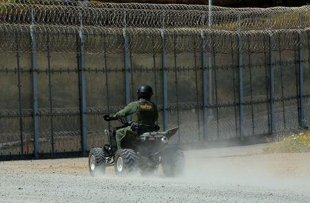 A U.S. border patrol agent patrols U.S. and Mexico border fence