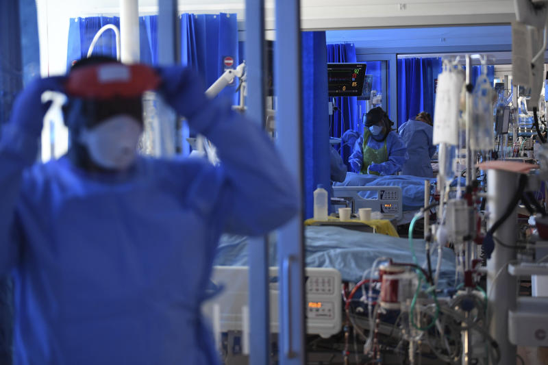 Members of the clinical staff wearing Personal Protective Equipment PPE care for a patient with coronavirus in the intensive care unit at the Royal Papworth Hospital in Cambridge, England, Tuesday May 5, 2020. (Neil Hall/Pool via AP)