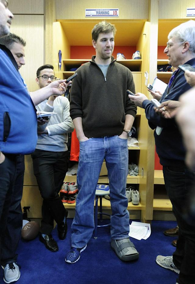 FILE - In this Dec. 30, 2013 file photo, New York Giants quarterback Eli Manning speaks to the media with a walking boot on his left foot after injuring his ankle in the last game of the season against the Washington Redskins, in East Rutherford, N.J. Eli Manning is going to start the offseason training program with a surgically repaired left ankle. The Giants announced that Manning will have arthroscopic surgery on Thursday, April 10, 2014, to relieve some lingering discomfort in the ankle he sprained in the regular season finale. (AP Photo/Bill Kostroun, File)