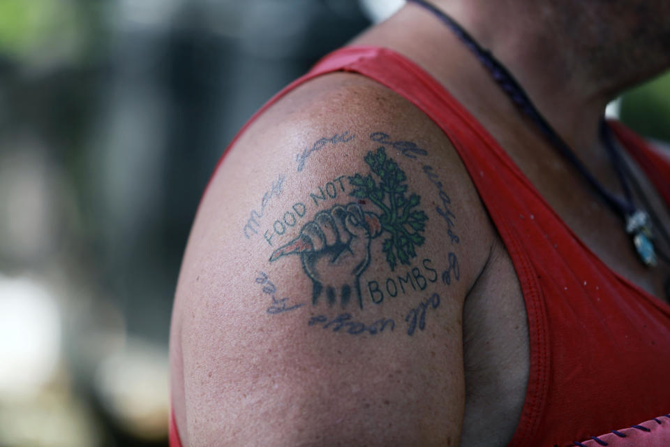 """A tattoo reading """"food not bombs"""" seen on the shoulder of a chef cooking in a kitchen at the annual Rainbow gathering on Friday, July 2, 2021, in the Carson National Forest, outside of Taos, N.M. More than 2,000 people have made the trek into the mountains of northern New Mexico as part of an annual counterculture gathering of the so-called Rainbow Family. While past congregations on national forest lands elsewhere have drawn as many as 20,000 people, this year's festival appears to be more reserved. Members (AP Photo/Cedar Attanasio)"""