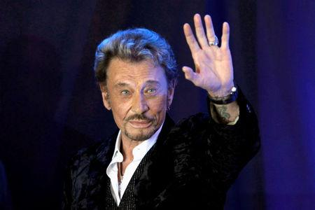 """FILE PHOTO: French singer Johnny Hallyday waves to fans attending a ceremony to promote his new album """"Jamais seul"""" (Never alone) at the Virgin Megastore in Paris"""