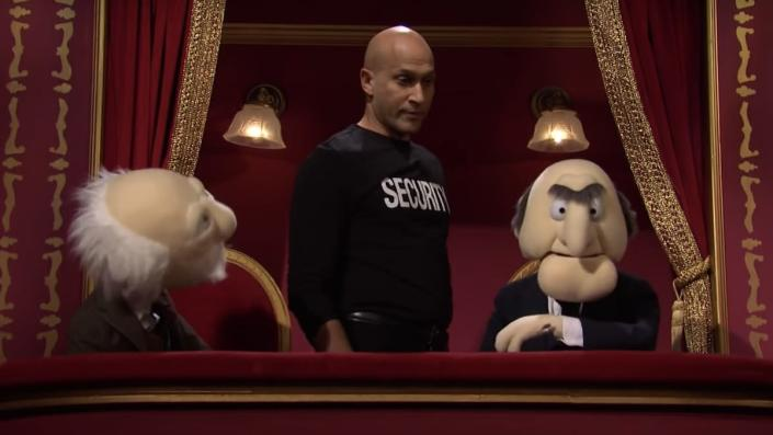 Keegan-Michael Key in a black security t-shirt stands behind Waldorf and Statler in their balcony box