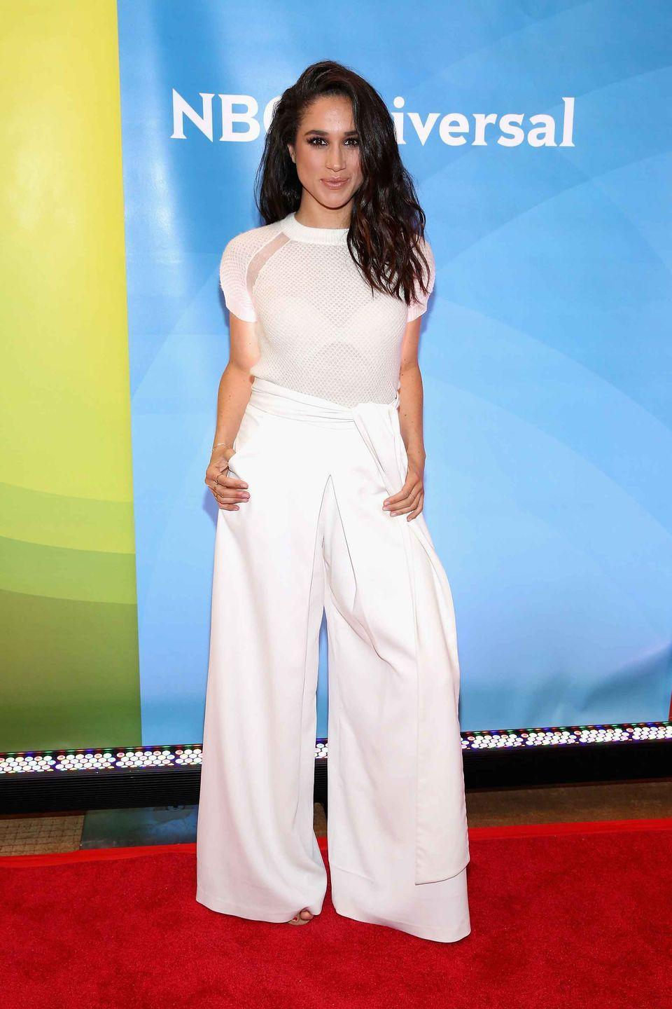<p>Markle makes a fashion statement in white flare pants while she attends NBC's 2015 New York Summer Press Day at the Four Seasons Hotel. </p>