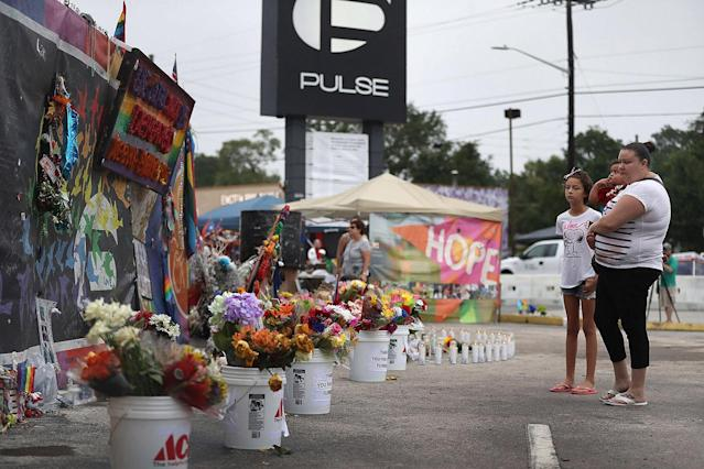 <p>People visit the memorial to the victims of the mass shooting setup around the Pulse gay nightclub one year after the shooting on June 12, 2017 in Orlando, Florida. (Joe Raedle/Getty Images) </p>