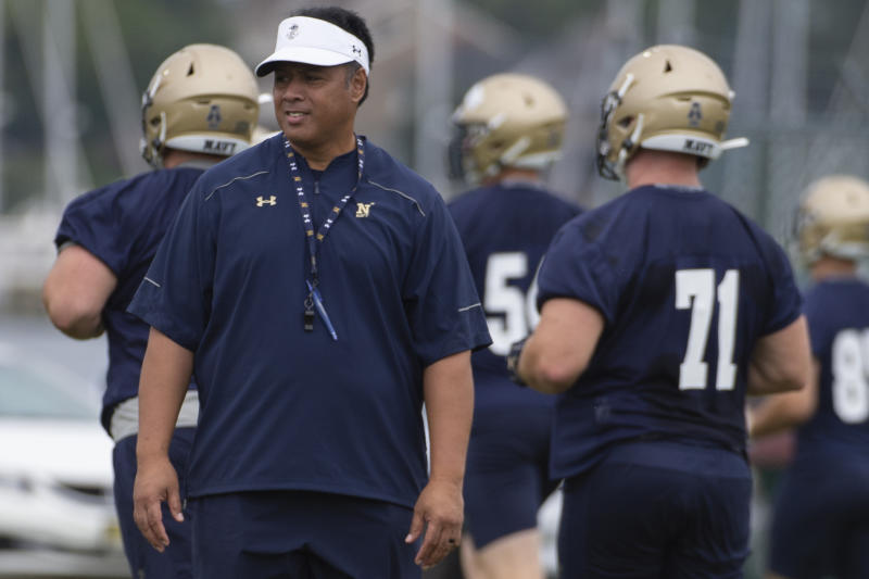Navy head coach Ken Niumatalolo stands on the field as players warm up for works out during NCAA college football training camp, Friday, Aug. 2, 2019, in Annapolis, Md. (AP Photo/Tommy Gilligan)