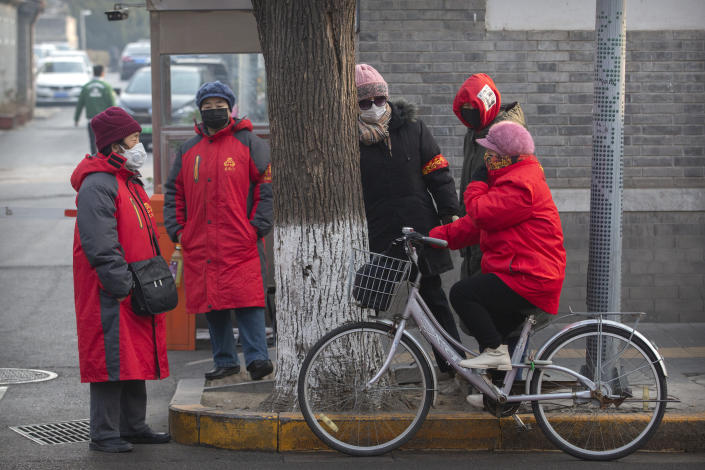 Neighborhood watch volunteers wear face masks as they gather on a street corner in Beijing, Monday, Jan. 27, 2020. China on Monday expanded sweeping efforts to contain a viral disease by postponing the end of this week's Lunar New Year holiday to keep the public at home and avoid spreading infection. (AP Photo/Mark Schiefelbein)