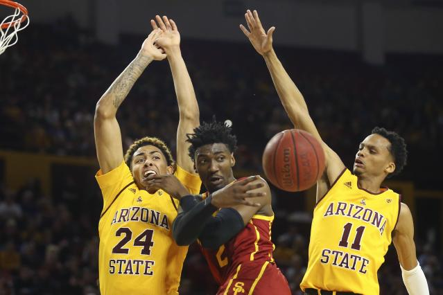 Southern California guard Jonah Mathews, center, passes the ball to a teammate as Arizona State forward Jalen Graham (24) and guard Alonzo Verge Jr. (11) defend during the first half of an NCAA college basketball game Saturday, Feb. 8, 2020, in Tempe, Ariz. (AP Photo/Ross D. Franklin)