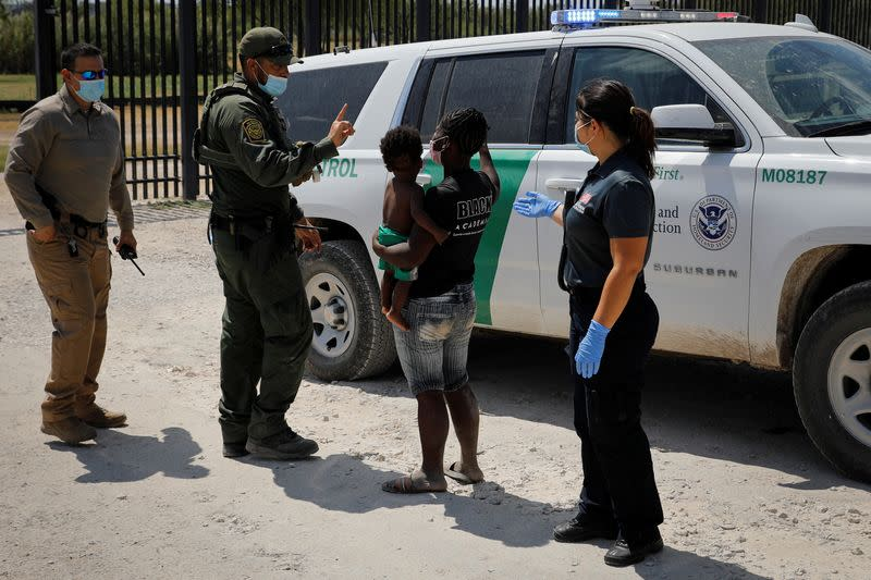 A U.S. CBP officer talks with a migrant seeking asylum in the U.S. near the International Bridge between Mexico and the U.S., in Del Rio
