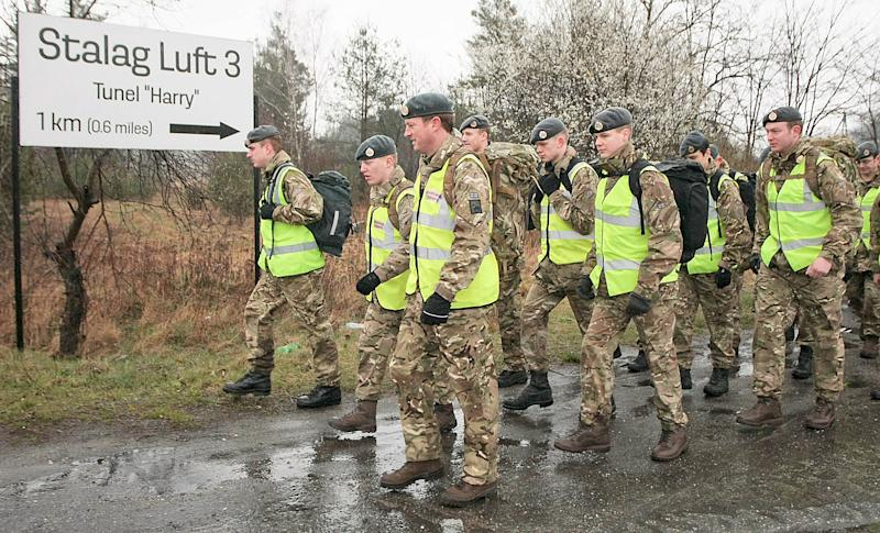 """A group of 50 British air force officers are marching from the site of the Nazi Stalag Luft III prisoner camp near Zagan, Poland, on Tuesday, March 25, 2014, to a British war cemetery in western Poland to mark 70 years since the Great Escape of Allied airmen and to honor 50 of them who were caught and executed. They started in rain from the place where 76 prisoners of war emerged from a tunnel on March 24 and 25, 1944. Only three airmen made it home. Fifty others were executed when caught, and 23 were sent to other camps, but survived the war. The 1963 Hollywood movie """"The Great Escape,"""" starring Steve McQueen, tells the story. (AP Photo) POLAND OUT"""