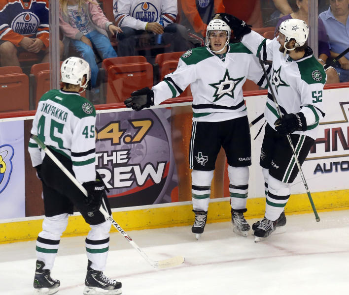Dallas Stars right wing Austin Smith, center, celebrates his first-period goal against the Edmonton Oilers with teammates Jyrki Jokipakka (45), of Finland, and Luke Gazdic (52) of Canada, in a preseason NHL hockey game in Oklahoma City, Friday, Sept. 27, 2013. (AP Photo/Sue Ogrocki)