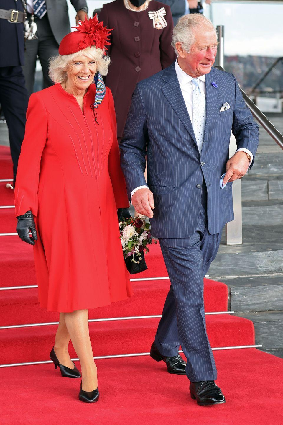 """<p>The Duchess of Cornwall matched the decor, wearing a red long-sleeved dress and hat in Wales. She accompanied Prince Charles and Queen Elizabeth to the <a href=""""https://twitter.com/ClarenceHouse/status/1448631216962473991"""" rel=""""nofollow noopener"""" target=""""_blank"""" data-ylk=""""slk:opening of the Senedd"""" class=""""link rapid-noclick-resp"""">opening of the Senedd</a> (the Welsh Parliament), where they were greeted by a 21-gun salute. </p>"""