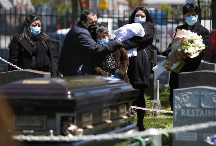 In this May 12, 2020 photo, the Rev. Joseph Dutan comforts his niece, Valerie Dutan, at the funeral of his father, Manuel Dutan, at St. John's Cemetery in the Queens borough of New York. Within one month, Dutan experienced the loss of his father and a fellow cleric, whom he considered a mentor. (AP Photo/Jessie Wardarski)