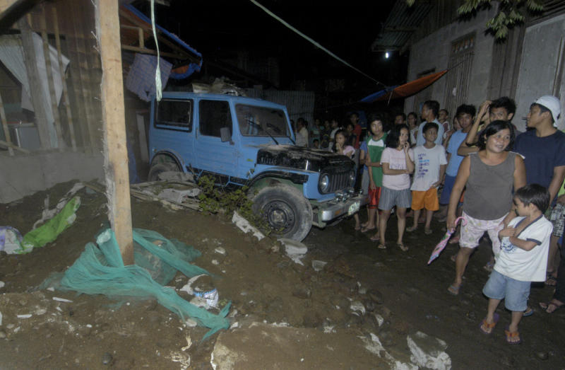 Residents gather at a collapsed house in Cagayan De Oro city, southern Philippines following a 7.6-magnitude earthquake that struck off the Philippines' eastern coast late Friday Aug.31, 2012. The quake set off car alarms, shook items off shelves and sent many coastal residents fleeing for high ground before authorities lifted all tsunami warnings they had issued for the Philippines and neighboring countries from Indonesia to Japan, and for Pacific islands as far away as the Northern Marianas. (AP Photo/Froilan Gallardo)