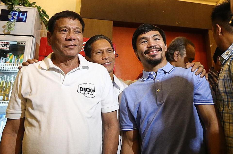 """Philippines' President-elect Rodrigo Duterte (L) stands beside boxing icon and newly elected Senator Manny Pacquiao (R) at a meeting in Davao in southern island of Mindanao on May 28, 2017.<span class=""""copyright"""">MANMAN DEJETO/AFP via Getty Images</span>"""
