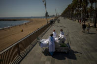 "Francisco Espana, 60, is surrounded by members of his medical team as he looks at the Mediterranean sea from a promenade next to the ""Hospital del Mar"" in Barcelona, Spain, Friday, Sept. 4, 2020. Spain has become the first western Europe to accumulate more than 1 million confirmed infections as the country of 47 million inhabitants struggles to contain a resurgence of the coronavirus. (AP Photo/Emilio Morenatti)"