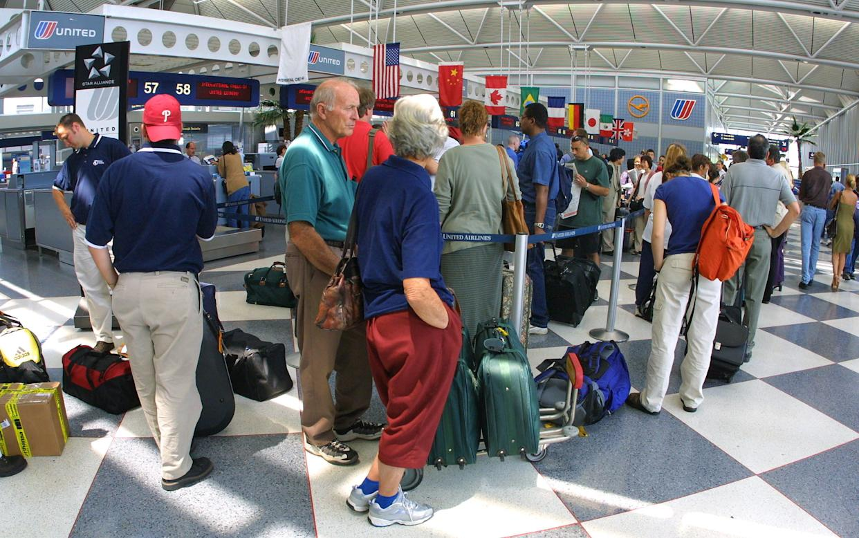 Travelers stand in line at the United Airlines terminal at O''Hare International Airport in Chicago, Illinois on June 18, 2001.