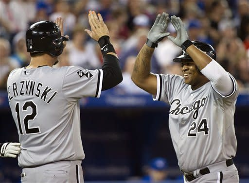 Chicago White Sox designated-hitter Dayan Viciedo, right, celebrates his solo home run with teammate A.J. Pierzynski, left, while playing against the Toronto Blue Jays during the seventh inning AL baseball game in Toronto on Wednesday, Aug. 15, 2012. (AP Photo/The Canadian Press, Nathan Denette)