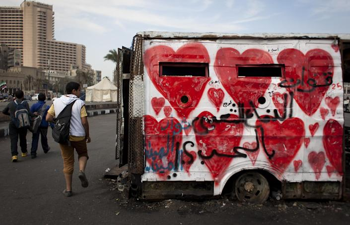 """Egyptian youths walk past a captured and burned police armored vehicle by demonstrators in the recent events, that is painted with red hearts and Arabic that reads """"the love popular defense forces,"""" in Tahrir Square, Cairo, Egypt, Tuesday, Feb. 19, 2013. An ultraconservative Islamist adviser to Egypt's president resigned Monday in solidarity with a fellow aide who was fired amid allegations of abuse of office. (AP Photo/Nasser Nasser)"""