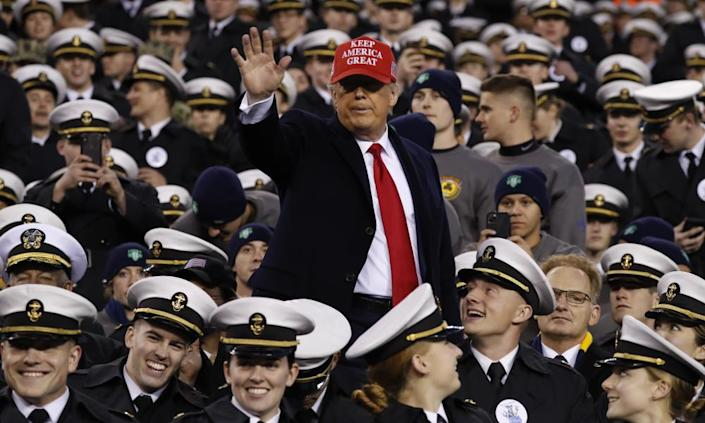 Donald Trump waves as he sits with Navy midshipmen in Philadelphia.
