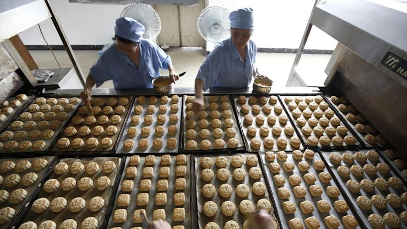 Freshly-baked mooncakes pass along a conveyor belt at a mooncakes factory in Shanghai September 12, 2013. With more calories than a Big Mac, mooncakes are traditionally given as gifts to family, friends and employees during China's Mid-Autumn Festival, which falls on Sept. 19 this year. But an anti-corruption drive by President Xi Jinping has left the pricier treats languishing on the shelves, shopkeepers and analysts say, even as sales of more traditional lotus seed- and sesame paste-stuffed varieties remain unhurt. Picture taken September 12, 2013.