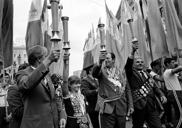 Holding a symbolic Olympic torch, former Soviet gold medalist Olga Korbut, center left, displays her many medals as she celebrates with others the arrival of the official Olympic Flame in Moscow, July 18, 1980. Opening ceremonies for the XXII Summer Olympics are scheduled for tomorrow. (AP Photo)
