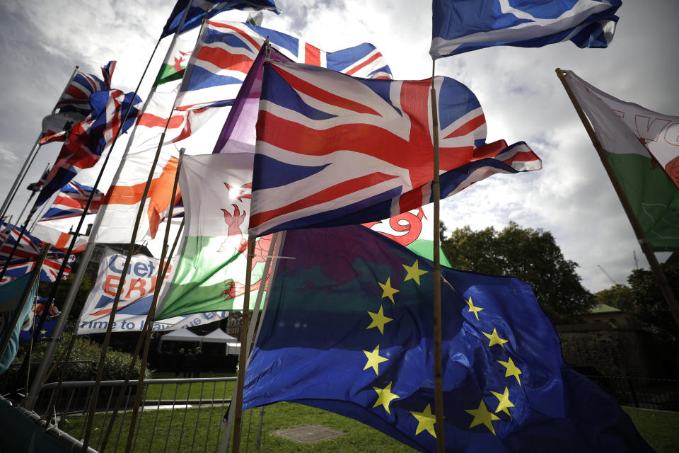 Flags, including a European flag, are blown by the wind after being placed there by Anti-Brexit remain in the European Union supporters near the Houses of Parliament in London, Wednesday, Oct. 15, 2019. The European Union and Britain sought to keep their chances of reaching a full Brexit divorce deal by Thursday's EU summit alive on Wednesday despite legal issues centering on the Irish border frustrating negotiators. (AP Photo/Matt Dunham)