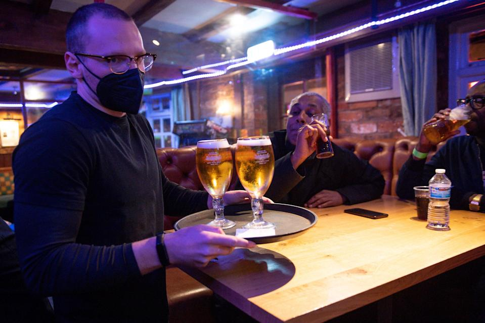 A man carries drinks in a pub (PA Wire)
