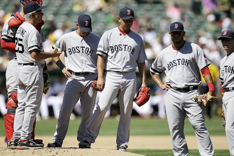 Boston Red Sox's Daisuke Matsuzaka, center, of Japan, waits to be relieved by Andrew Miller after being removed by manager Bobby Valentine in the fourth inning of a baseball game against the Oakland Athletics, Sunday, Sept. 2, 2012, in Oakland, Calif. Matsuzaka gave up six runs in 4 2/3 innings. (AP Photo/Ben Margot)
