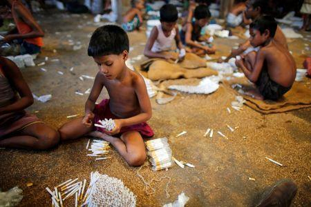 Children fill up empty cigarettes manually with locally grown tobacco in a small bidi (cigarette) factory at Haragach in Rangpur district